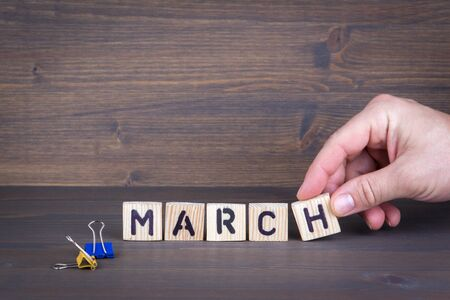 march. Wooden letters on the office desk, informative and communication background.