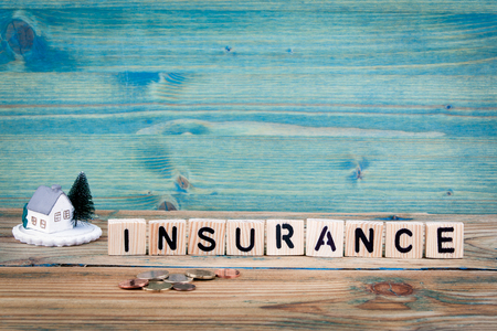 miniature model of house and wooden letter text: insurance.