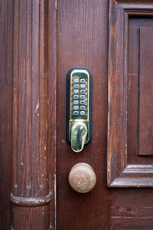 gold color code key on brown wooden door. Archivio Fotografico