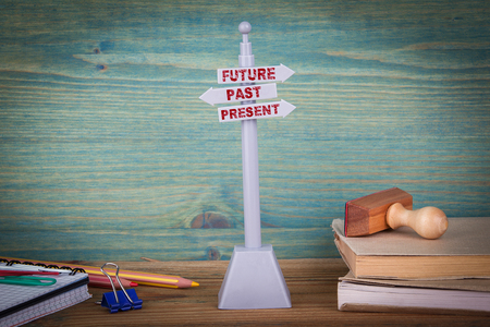 future, past and present. Signpost on wooden table.