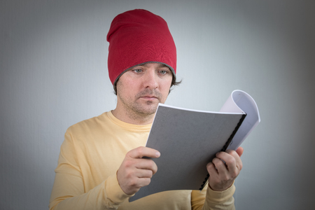Young man with red hat interested in reading gray notebook. 写真素材