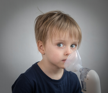 Little boy takeing inhalation for respiratory didease.