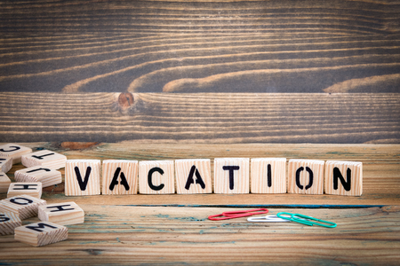 Vacation. Wooden letters on the office desk, informative and communication background. Stock Photo