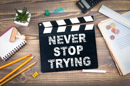 Never stop trying. Movie clapper on a wooden desk.