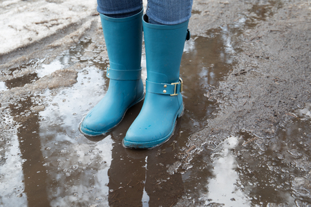 Standing in puddle in rubber boots, spring, melting snow.