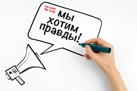 we want the truth, English and Russian. Megaphone and text on a white background. Stock Photo