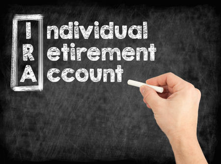 IRA - Individual Retirement Account concept. Hand writing by white chalk on a blackboard. Stock Photo - 100854593