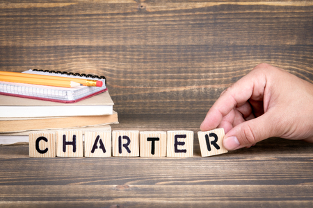 charter. Wooden letters on the office desk, informative and communication background