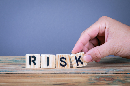 risk. Wooden letters on the office desk, informative and communication background