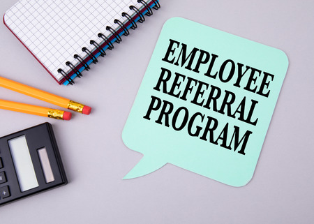 Employee Referral Program. Paper speech bubble on a gray table