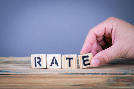 rate. Wooden letters on the office desk, informative and communication background