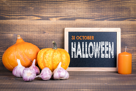 Halloween 31 October, pumpkins, candle and garlic on a wooden background Stockfoto