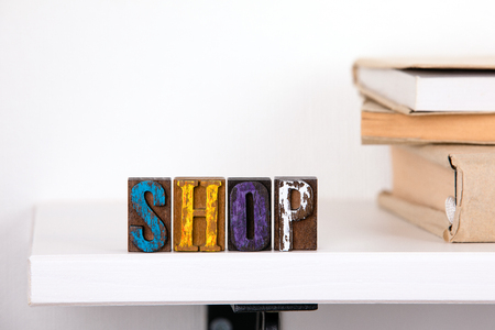 Shop word from colored wooden letters un the whitte shelf near books