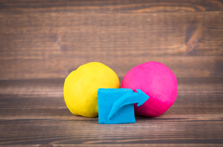 share icon from plasticine and multiple colorful balls on wooden background