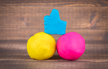 like hand icon from plasticine and multiple colorful balls on wooden background Imagens