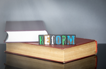 Reform word from colored wooden letters on gray background. Education and knowledge concept