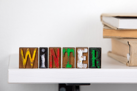 Winter word from colored wooden letters un the white shelf near books