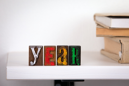 Year - word from colored wooden letters un the whitte shelf near books Stockfoto