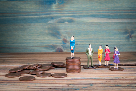 Miniature people standing on piles of coins. Income and economic inequality concept