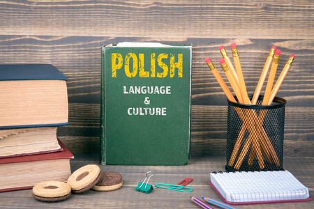 Polish language and culture concept. Book on a wooden background