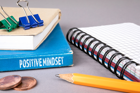 positive mindset concept. blue book on a gray office table. communication and information
