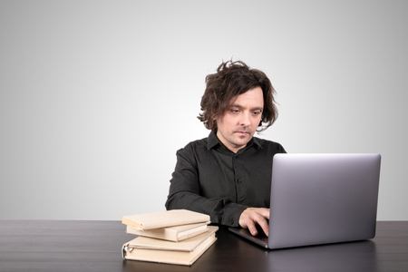 Skills, knowledge and learning online concept. Businessman working on laptop at office. Gray background with copy space