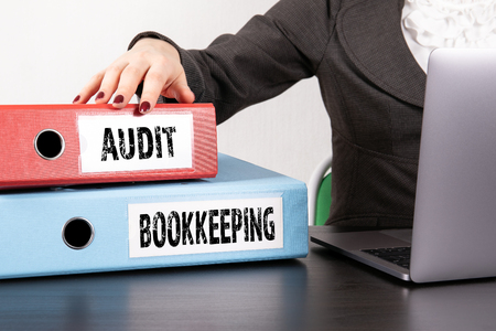 Audit and Bookkeeping concept. Two binders on desk in the office. Business woman with laptop