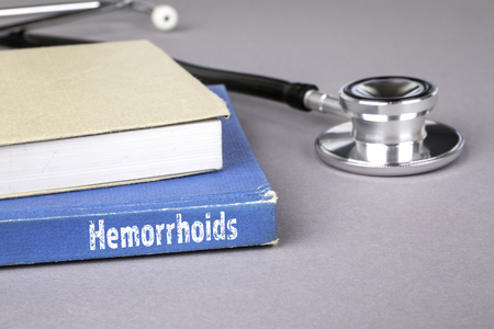Hemorrhoids. Blue book on a gray office table. Communication and information Imagens