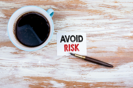 Avoid Risk concept. Paper letter and pen on a wooden table Stock Photo