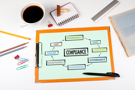 Compliance concept. Chart with keywords. Office desk with stationery