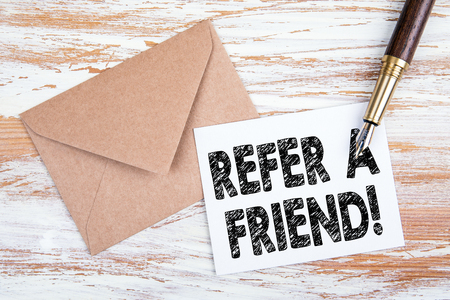 Refer a friend. Paper letter and pen on a wooden table