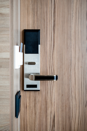 Electronic card smart lock on wooden door at the hotel for power. Banque d'images - 121845192