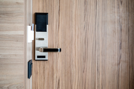 Electronic card smart lock on wooden door at the hotel for power. Banque d'images - 121845208