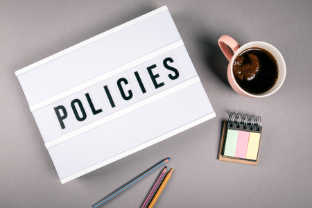 Policies. Text in light box. Pink coffee mug on gray background