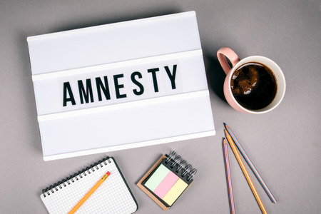 Amnesty. Text in light box. Pink coffee mug on gray background