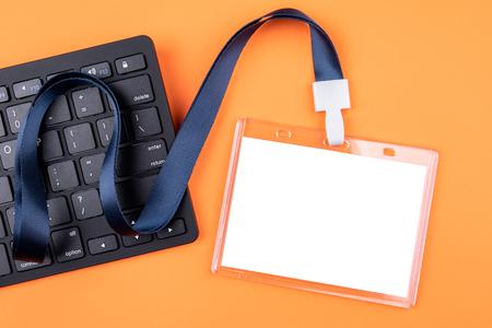 Maquette d'identité du personnel vide blanc avec lanière bleue. Porte-nom, carte d'identité. Clavier d'ordinateur sur fond orange