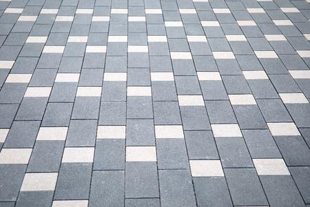 Grey brick stone street road. Sidewalk, pavement texture background