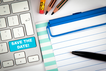 Speichern Sie das Datumskonzept. Computertastatur auf einem weißen Schreibtisch mit verschiedenen Gegenständen