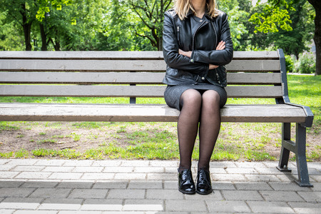 Woman crossing hands over chest sitting in the park, body language concept Imagens