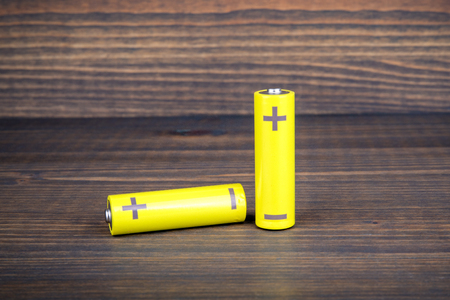 Yellow AA size batteries on wooden background