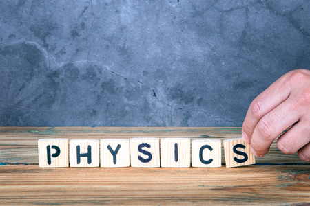 Physics - word from wooden letters on wooden table