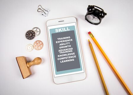 Skill Concept. Smartphone on white table. Stationery and clock