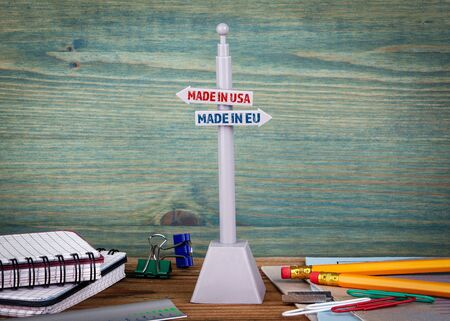 Made in USA and EU. Trade war. Signpost on a wooden desk Banco de Imagens