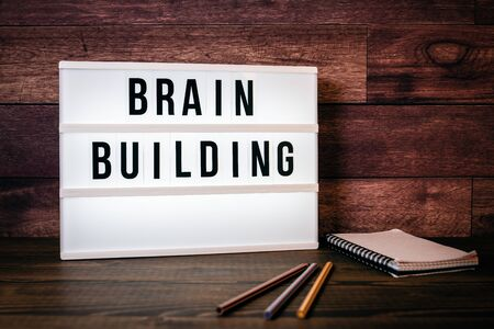 Brain Building. Text in lightbox. Wooden office table Stock Photo - 125886841
