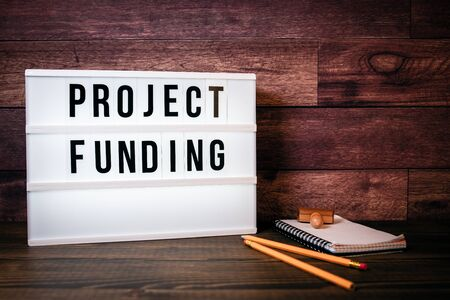 Project Funding. Text in lightbox. Wooden office table