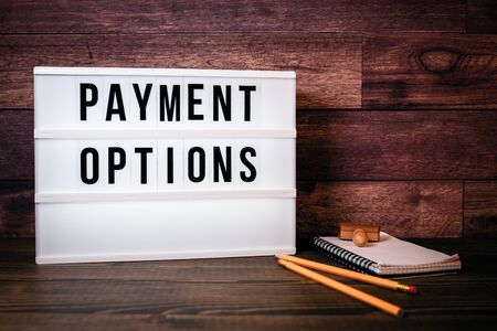 Payment Options. Text in lightbox. Wooden office table Stock Photo