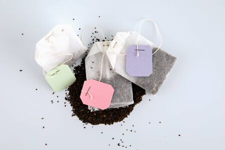 Teabags with spilled tea and label. Top view, on a white background. Mockup Stock Photo - 125886823