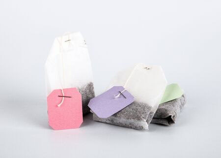 Teabags with pink, green and purple label. Top view, on a white background. mockup Stock Photo - 125886826