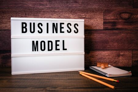 Business model. Text in lightbox. Wooden office table Stock Photo - 125886827