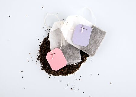Teabags with spilled tea and label. Top view, on a white background. Mockup